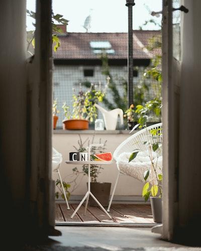 balcon avec deux sièges, une table d'appoint et des plantes